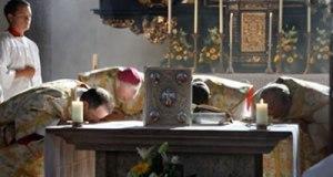 Sacerdote y diáconos besando el altar.